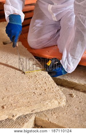 Man cutting rockwool panel to fit in thermal insulation layer - closeup on hands