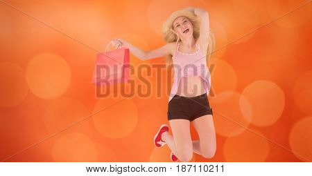 Digital composite of Happy woman with shopping bag jumping over bokeh
