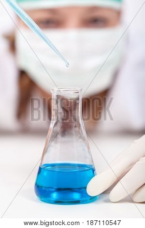 Lab technician dropping reagent into an erlenmeyer flask - closeup on flask