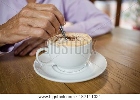 Close up of woman stirring coffee while sitting at table in cafe
