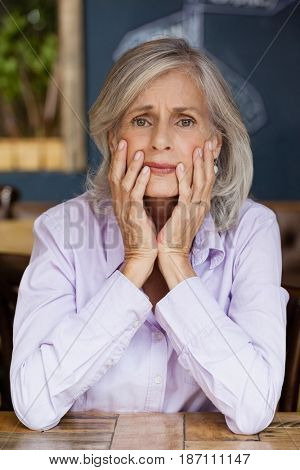 Portrait of worried senior woman sitting at table in cafe shop