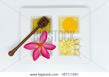 Set of healthcare beauty treatment garlic capsule honey and egg yoke on white ceramic plate and wooden spoons.