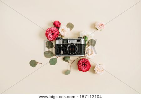 Vintage retro camera red and beige rose flower buds pattern on pale pastel beige background. Flat lay top view decorated concept.