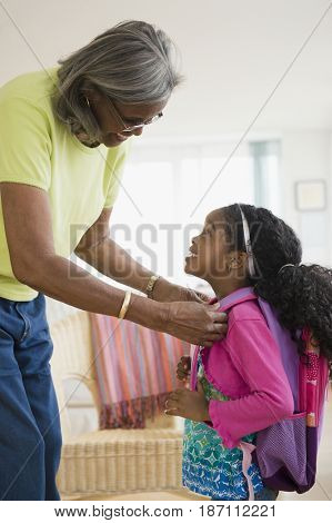 African American woman helping granddaughter with backpack