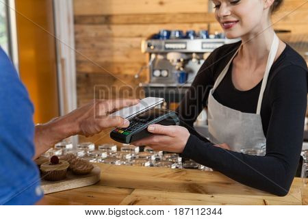 Close up of man making payment on credit card reader machine at cafe shop