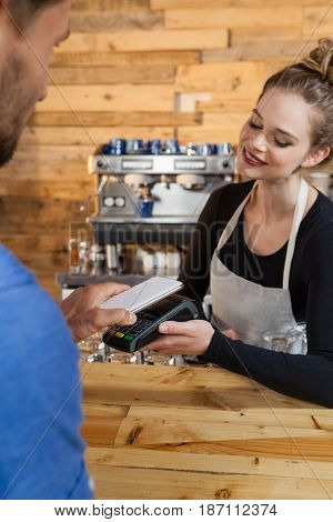 Customer making payment on credit card reader machine at cafe shop