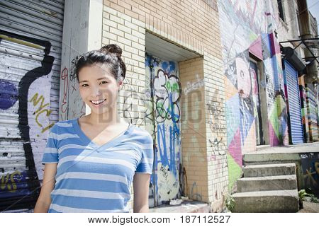 Asian woman near urban graffiti