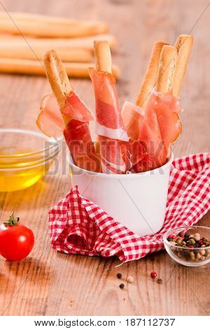 Grissini breadsticks with ham and olive oil on wooden table.