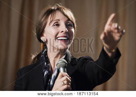 Caucasian businesswoman speaking into microphone