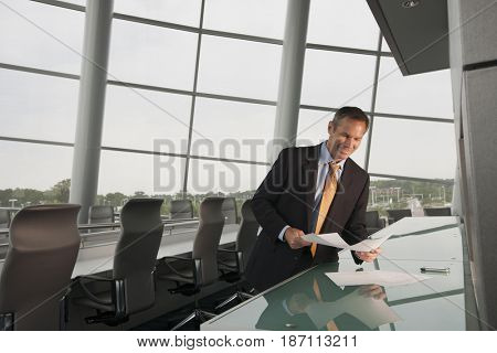 Caucasian businessman looking at paperwork in conference room