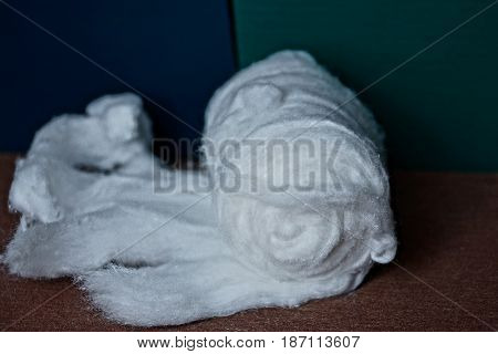 Unwound roll of white cotton on the table