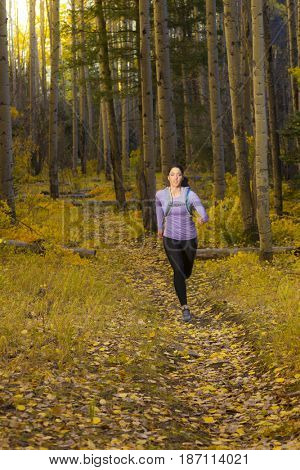 Hispanic woman running in woods
