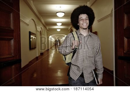 Student with afro walking in corridor