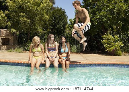 Girls watching teenage boy jumping in to swimming pool