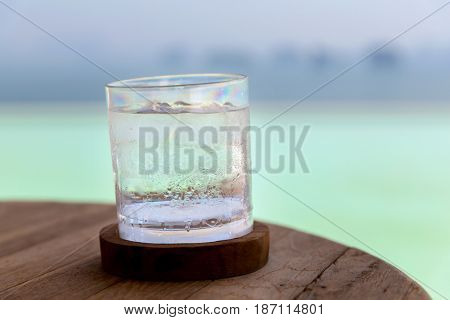 drinks and luxury concept - glass with cold water or cocktail on bar table