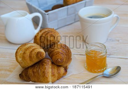 Cup of coffee small milk jug and croissants with peach jam on rustic wood table. Traditional French breakfast.