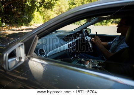 Young man using mobile phone while driving car