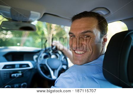 Driver smiling at camera from front seat in the car