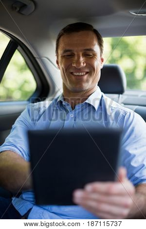 Smiling man using digital tablet in car