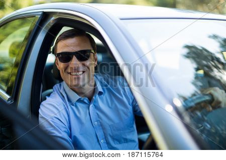 Portrait of man wearing sunglasses while driving car