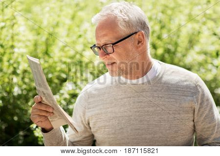 mass media, news and people concept - senior man reading newspaper in city