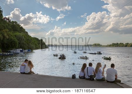 BELGRADE SERBIA - MAY 13 2017: Young people sitting on Zemun Quay (Zemunski Kej) at sunset watching sunset over Danube river