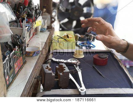 Watch repair craftsman repairing watch in Technology background