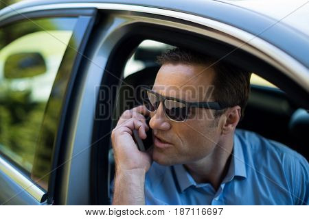 Close up of young man talking on phone while driving car