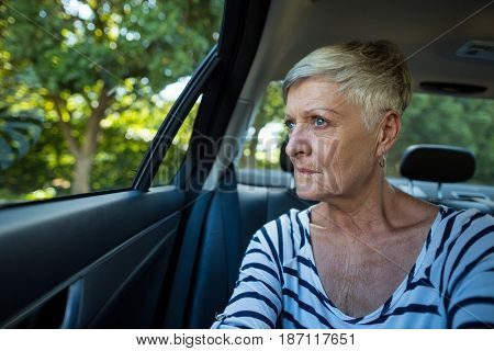 Serious senior woman looking through car window