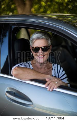 Portrait of smiling senior woman sitting in car