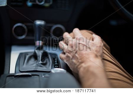 Mid section of senior man sitting in car