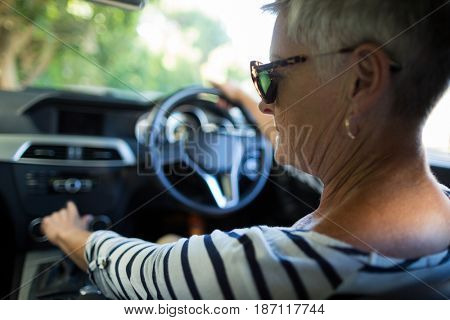Rear view of serious senior woman driving car