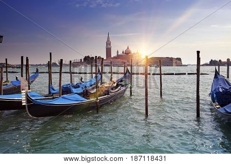 Venice. A sunset over the channel Grande and gondolas at the mooring