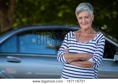 Portrait of confident senior woman standing by car