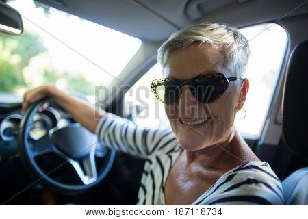 Close up portrait of senior woman driving car