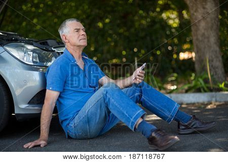 Thoughtful senior man sitting by car on road after breakdown