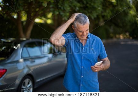 Tensed senior man using mobile phone by car on road