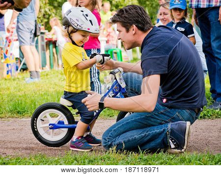 Russia. Moscow. Vorontsovsky Park on the 21st of August. STRIDER CUB 2016. Children go to the balancebike along the path in the park. My father encourages his son