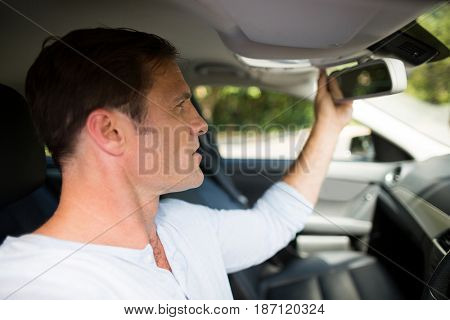 Young man adjusting rearview mirror in car