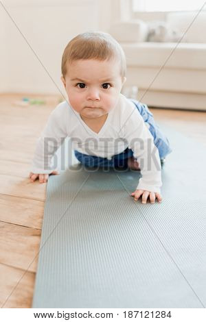 Funny Baby Boy Crawling On Yoga Mat With Angry Expression