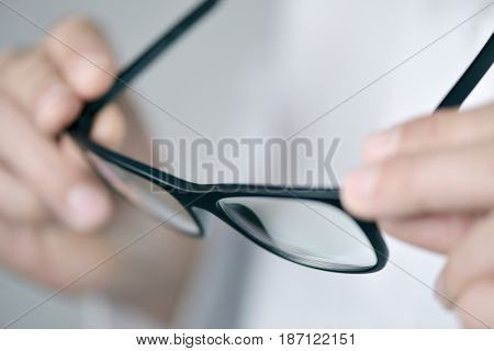 closeup of a young optician man in a white coat checking a pair of eyeglasses
