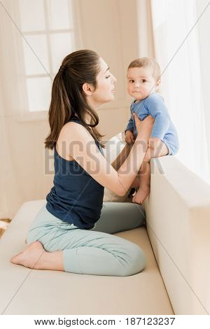 Mother With Baby Boy In Casual Clothes Able To Kiss On Couch At Home. Young Loving Family Concept