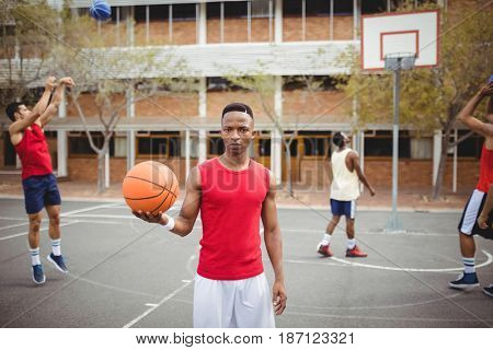 Portrait of male basketball player holding basketball in basketball court