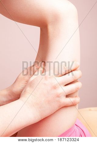 Elementary age girl's thigh being manipulated by an osteopath - an alternative medicine treatment