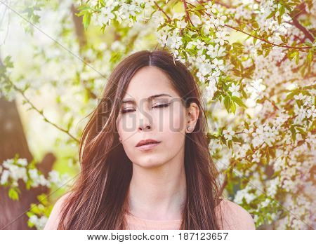 Romantic girl closeup face with close eyes, cherry blossom on the background. Pretty young woman dreaming about something closing eyes, spring time, sinny day.
