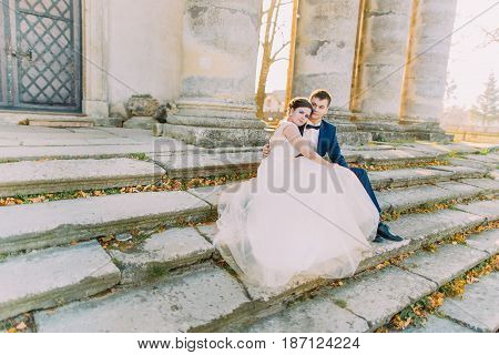 Lovely photo of the newlyweds sitting on the stairs of the old castle and looking at the right side