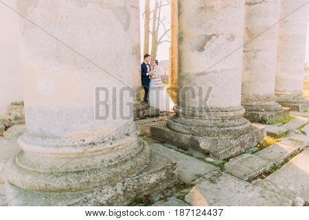 The newlyweds are holding hands and standing among columns