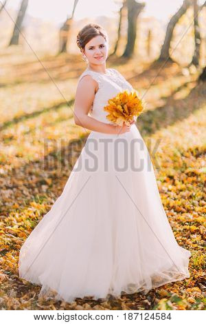 The full-length view of the smiling bride holding the bouquet of the yellowed leaves