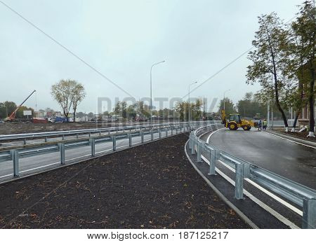 Road junction with lawn in the front. Construction vehicles and workers at the back. Cloudy rainy day. City landscape. Soft focus.