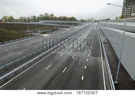 Empty gray highway, outgoing to the horizon. Road junction with sidewalk in the front. Cloudy rainy day. City landscape. Soft focus.